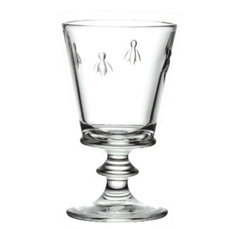 A clear wine glass with four bees embossed on it.