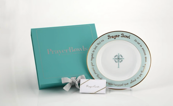 "Pictured is the Angie Prayer Bowl next to its packaging and a stack of prayer cards. The packaging is a square, flat, baby blue box with silver lettering on the front that say ""Prayer Bowls,"" and a silver ribbon holding the lid closed."