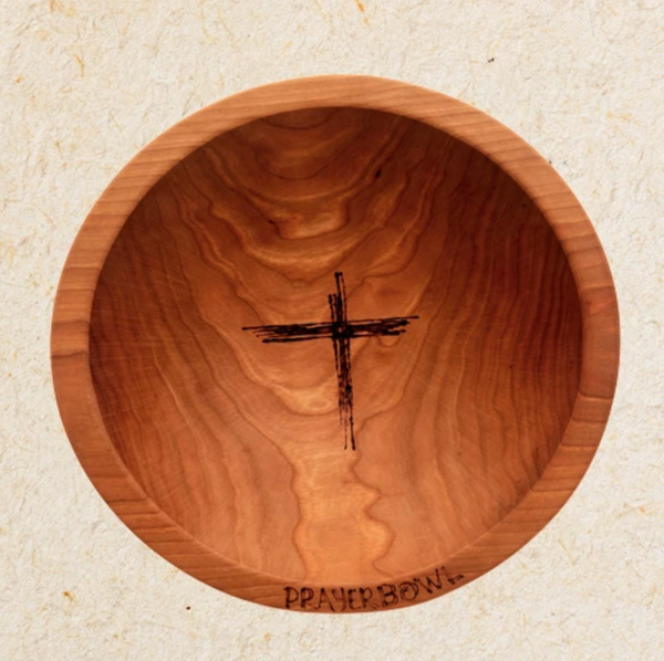 "Pictured is the Noah Prayer Bowl. It is carved from wood and has a warm finish. The shape of the bowl is very simple. There is a rough carving of a cross in the center of the bowl's basin. On the bottom edge lip of the bowl are carved the words ""PRAYER BOWL."""