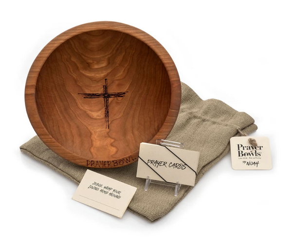 Pictured is the Noah Prayer Bowl displayed on top of its burlap sack packaging. Next to it is a stack of the prayer cards that come with it.