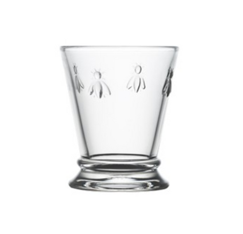 A clear glass mini tumbler with four embossed bees on opposite sides. It is in the shape of a tumbler glass but is shorter.