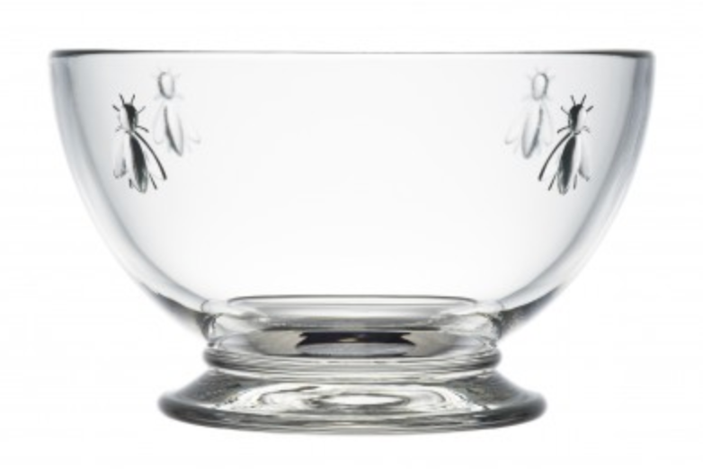 A clear glass bowl with four bee designs embossed on opposite ends from one another is pictured.