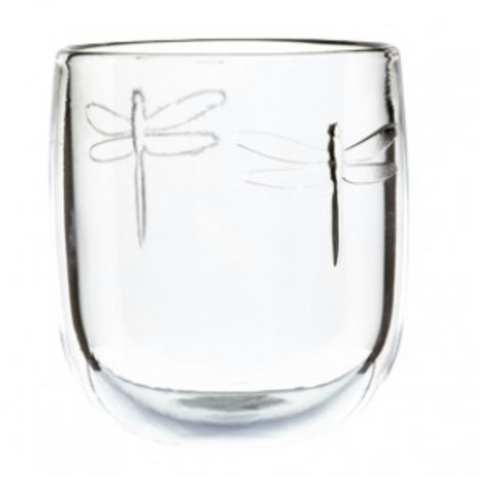 A short tumbler glass with two dragonfly designs embossed on it.
