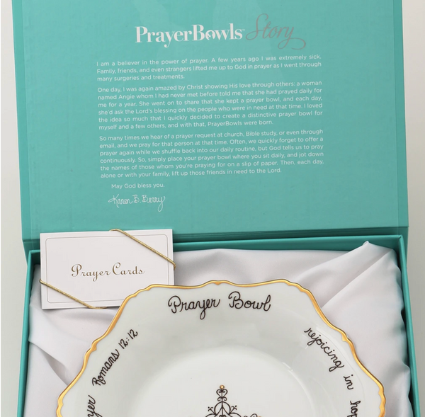 Pictured is an open Prayer Bowl box, showing the Celeste Prayer Bowl and prayer cards inside. On the inside lid the Prayer Bowls story is printed.