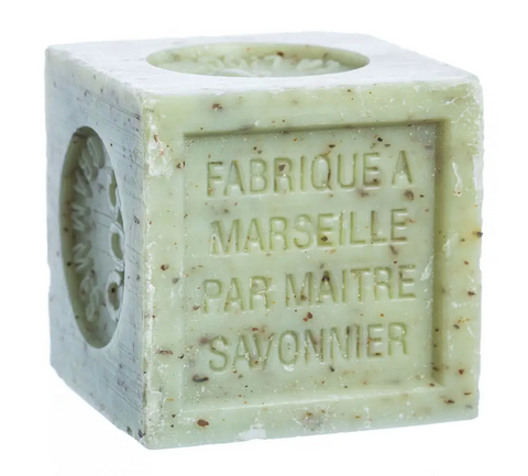 "Pictured is a verbena soap block by Savon de Marseille. It is a light green cube of soap with brown flecks in it. Etched into the side of it are the words ""FABRIQUE A MARSEILLE PAR MAITRE SAVONNIER."""
