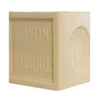 Pictured is a block of palm oil soap by Savon de Marseille. Etched into the side of it is the name of the brand. It is cream in color.