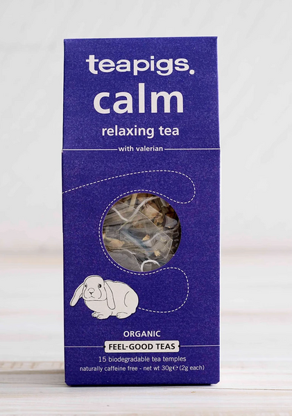 "Pictured is the packaging for Teapigs Organic Calm Tea. It is a rectangular box that is dark blue and has the image of a white bunny on it. There is a circle of clear plastic to show the teabags inside the packaging. The label of the package reads ""teapigs calm relaxing tea with variation organic feel-good teas."""