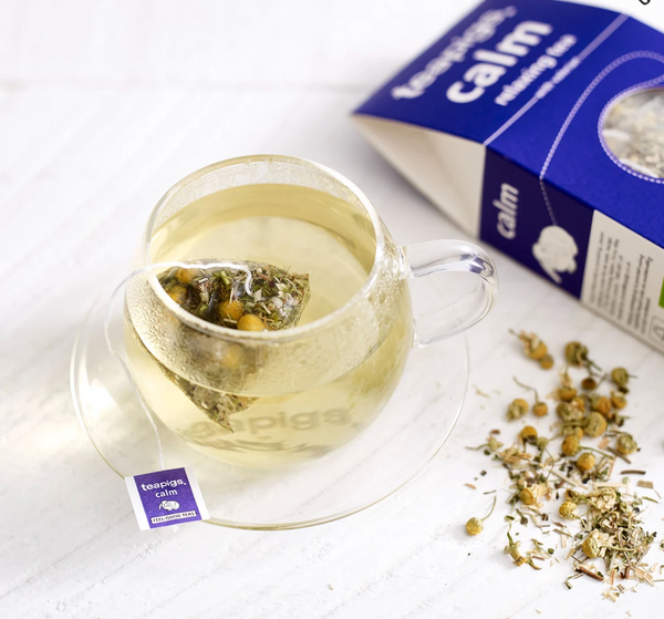 Pictured is a cup of tea next to loose tea and an open package teapigs organic calm tea.