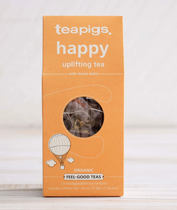 "Pictured is the packaging for Teapigs Organic Happy Tea. The box is a light orange color and has a design of a tiny hot air balllon. There is a small round clear plastic window through which the teabags can be seen. The label on the packing reads ""teapigs happy uplifting tea with lemon balm organic feel-good teas"""