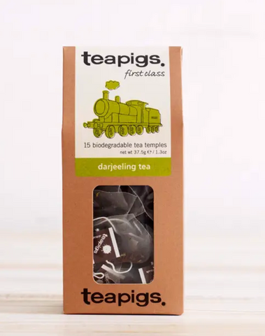 "Pictured is the packaging for Teapigs Darjeeling Tea. It is a tall brown box with a clear plastic window showing the teabags. The label is white with a green steam engine design. The label reads ""teapigs first class 15 biodegradable tea temples darjeeling tea."""