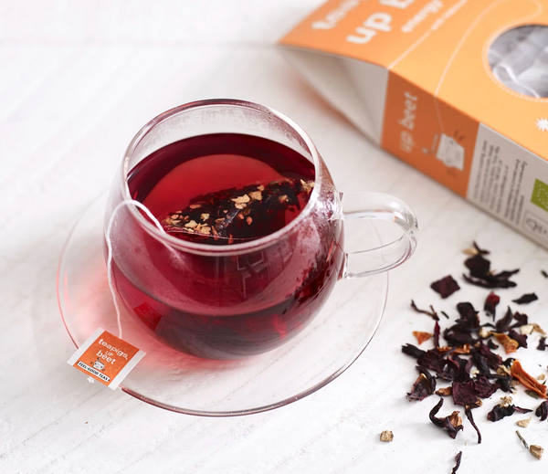 Pictured is a cup of tea next to loose leaf tea and a package of teapigs organic upbeet tea.