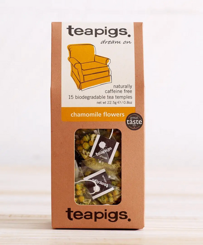"Pictured are the Teapigs Chamomile Flowers in their packaging. The pacakging is a brown box with a little clear window in the center, through which the teabags are visible. On the packaging is a white and yellow label with an image of a comfy armchair. The label reads ""teapigs dream on,"" ""naturally caffeine free 15 biodegradable tea temples,"" ""chamomile flowers."""