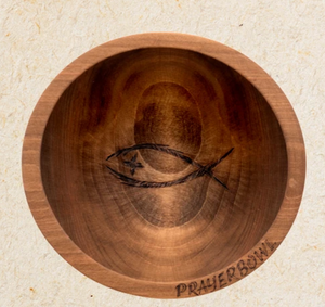 "Pictured is the Randolph Prayer Bowl. It is a simple, shallow bowl carved from wood. In the center is a carving of an ichthys with a cross for an eye. On the bottom edge of the bowl is a carving of the words ""PRAYER BOWL"""
