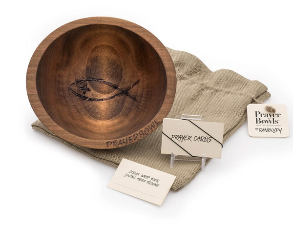 Pictured is the Randolph Prayer Bowl sitting on top of its burlap sack packaging, next to a stack of prayer cards that come with it.