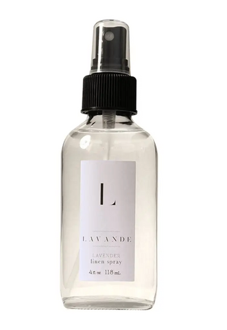 Pictured is a glass spray bottle of Lavande Linen Spray. The liquid inside is clear. The bottle has a white Lavande label sticker on it.