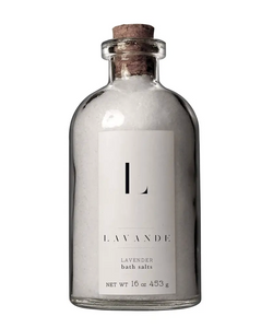 "It is a glass bottle with a cork in the top. It is filled with lavender bath salts. The bottle has a white label that reads ""L LAVANDE LAVENDER bath salts"""