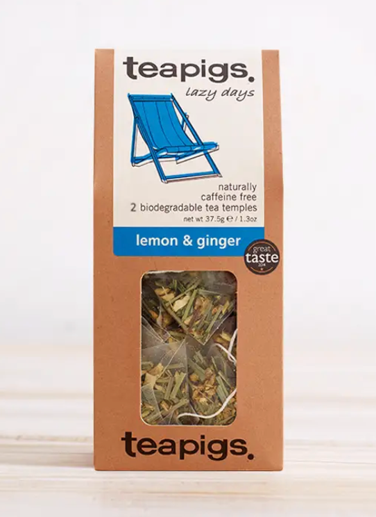 "Pictured is the packaging for lemon & ginger Teapigs tea. It has a clear plastic window to display the teabags inside. The label is white with a blue beach chair and the words ""teapigs lazy days naturally caffeine free 2 biodegradable tea temples lemon & ginger"""