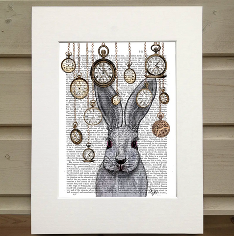 Pictured is a page from a book framed with mat. Printed over the book page is the head and shoulders of a rabbit surrounded by pocket watches hanging from their chains from the top of the page, all hanging at various heights.