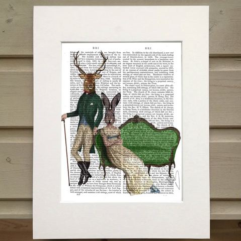 Pictured is a page from a book framed with mat. Printed over the page are two figures and a couch. One figure wears an old horesback riding outfit and holds a cane. The other sits on an old fashioned green couch. The figure on the couch wears on old dress with an empire waist. The figure standing has the head of a deer with antlers. The figure sitting on the couch has the head of a rabbit or hare.