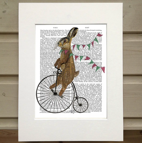 There is a page from a book framed with mat. Printed over the words on the page is a bunny riding an old fashioned bicycle that has a large wheel in the front and a small wheel in the back. Around the neck of the rabbit is a bunting with green and red flags, as if the bunny is crossing a finish line or wearing it like a scarf.