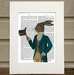 A page from a book is framed with mat. Printed over the page is a figure wearing an old fashioned outfit. He wears a turquoise coat, a mustard vest, a white turtleneck poufy shirt, and kahki pants. The figure has the head of a hare rather than the head of a man. He holds a tophat as if he's tipping it toward the viewer. In his other hand is a cane.