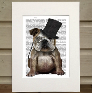 Pictured is a page out of a book framed with a mat. Printed over the page is the image of a cute bulldog wearing a monocle and a tophat.