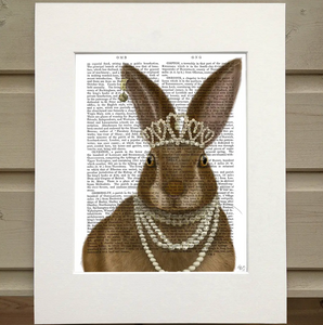 There is a page from a book framed with mat. Printed over the words on the page is the image of a bunny wearing several pearl necklaces, a crown of pearls, and an earring with a bell in one ear.