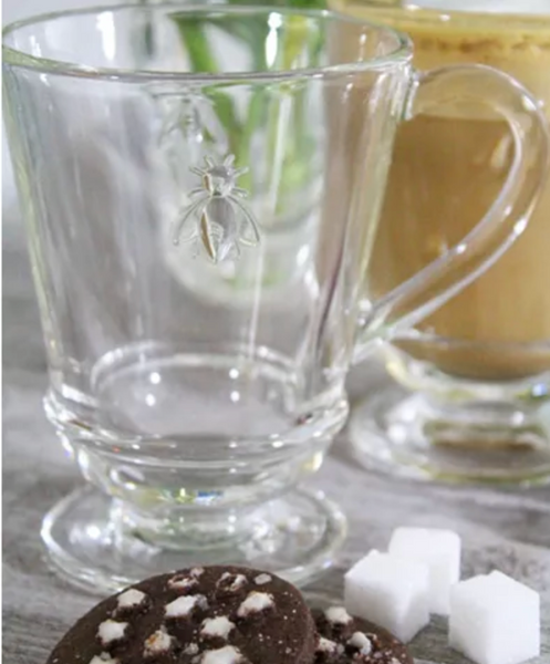 A bee coffee mug sits on a table next to 3 sugar cubes and 2 chocolate desserts.