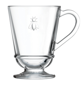 A glass coffee mug with a bee embossed on it. It is cylindrical in shape.