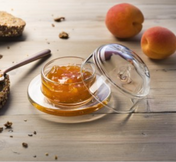 A glass bee butter dish sits on a table with peaches and cut pieces of whole wheat bread. The dish has some kind of peach marmalade or jam inside of it.