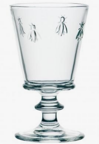 A clear water glass with four bees embossed on it. It has a decorative stem and is cylindrical in shape.