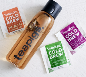 There is a packet of Teapigs Cold Brew in peach and mango, cucumber and apple, and lychee and rose. They are scattered around a water bottle full of tea that has the teapigs logo on it.