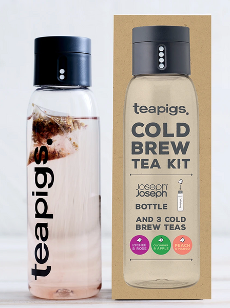 Pictured is the packaging for the Teapigs Cold Brew Tea Kit. It is a rectangular brown box with an image of the teapigs water bottle on it. Next to the box is a teapigs water bottle filled with tea.