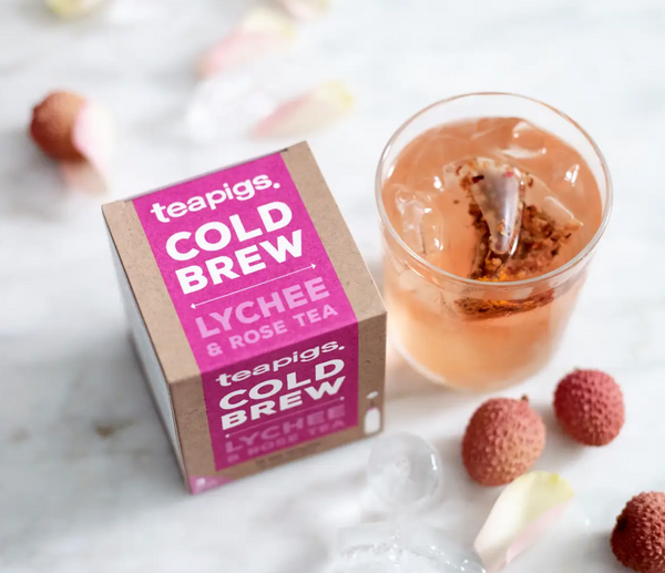 Pictured from above is a package of Teapigs Cold Brew Lychee and Rose tea next to a glass of ice water with a teabag in it. Surrounding the package and the glass are lychee fruits and rose petals.