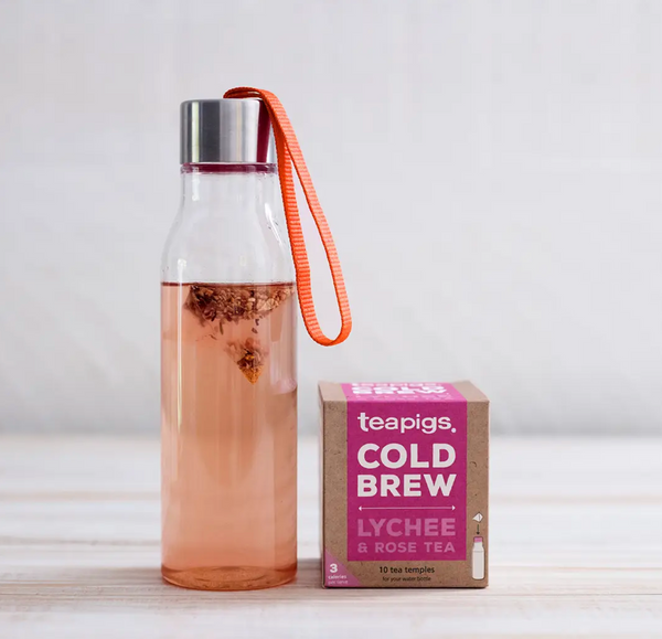 There is a reusable water bottle with water and a teabag inside. It sits next to a package of Teapigs Cold Brew Lychee and Rose tea.