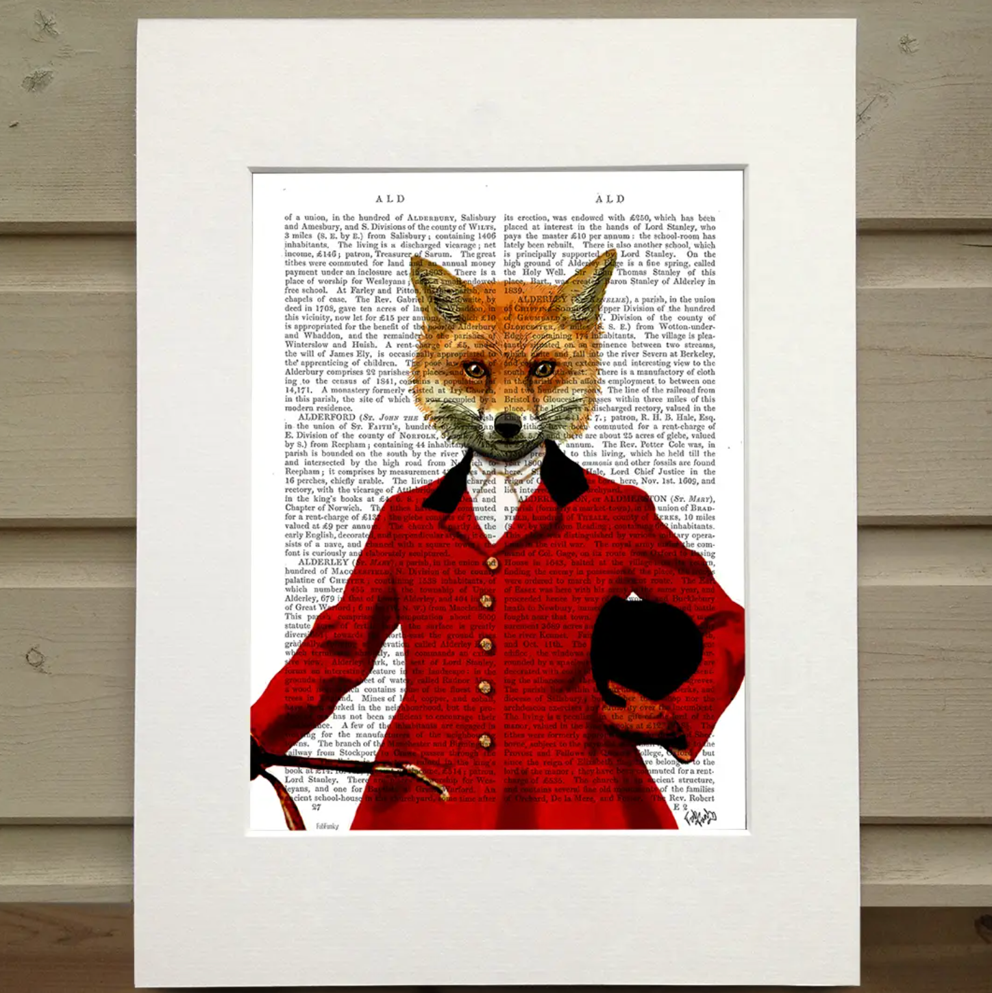 A page from a book is framed with mat. Printed over the page is a figure wearing an old hunting outfit with a red coat. In their left hand is the crop and tucked under their right arm is their riding helmet. Instead of the head of a person they have the head of a fox. This image is a portrait of the fox figure, cropped at the figure's waist.