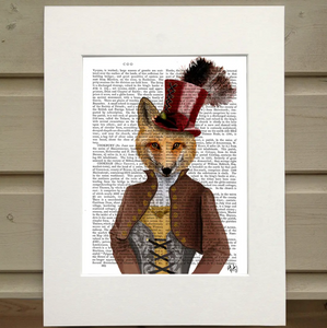 Pictured is a page out of a book framed in mat. An opaque print of a figure is over the page. The figure wears an old fasioned outfit with a corset top and a jacket with a popped collar, and a top hat with a feather sticking out of the top. The figure has the head of a red fox instead of that of a human.