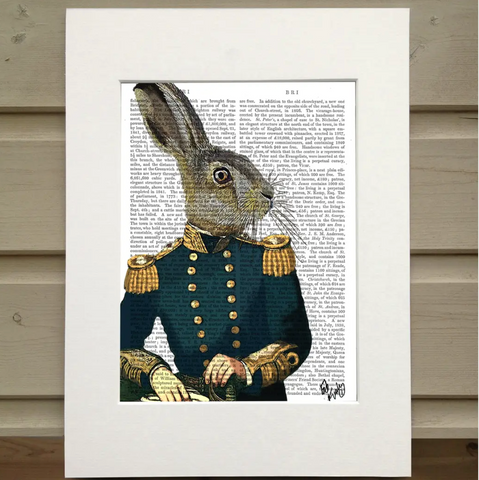 There is a page out of a book framed in mat. Printed over the page is a figure visible from the waist up. It wears a blue military uniform with gold buttons and accents. Instead of having the head of a man, the figure has the heads of a hare.