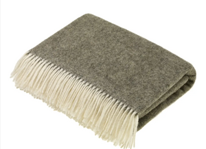 Pictured is a folded blanket. It is grey and textured. It has white tassels hanging off of the edge.