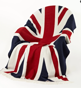 Pictured is a chair covered with a blanket in the pattern of the Union Jack. It has white tassels on its edge.