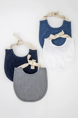 Pictured are four linen baby bibs. There are two on the left, one stacked on top of the other. The bib on top is a thin railroad stripe pattern, with a dark denim bib below it. The two bibs on the right are also stacked on top of each other. The bib on top is white demin and the one below it is light denim.