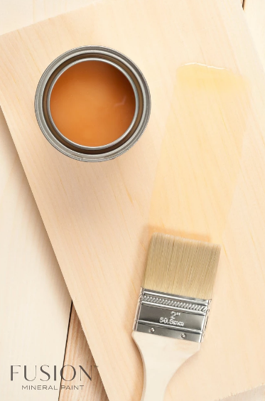 Pictured from above is an open can of Fusion Stain and Finishing Oil. It sits on a piece of wood that a paintbrush is brushing the Stain and Finishing Oil onto.