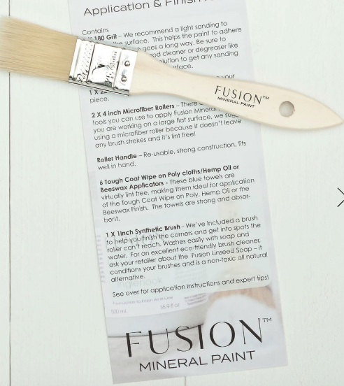 Pictured is a paint brush laying on top of a list of the contents of the Fusion Paint Kit.