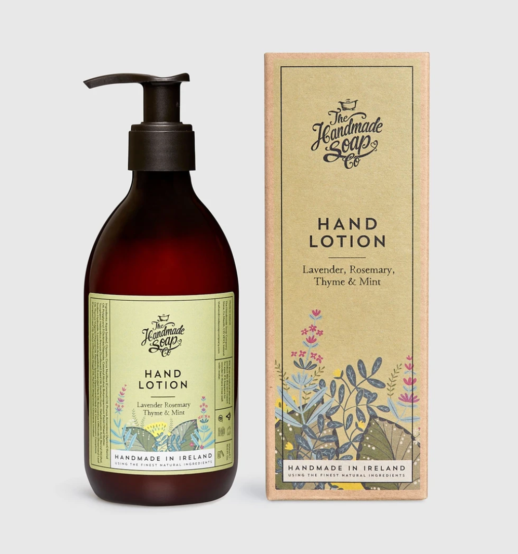 "Pictured is a tinted glass lotion container with a pump lid. The label of the container reads ""The Handmade Soap Co. HAND LOTION Lavender, Rosemary, Thyme, & Mint HANDMADE IN IRELAND."" Next to the bottle of lotion is the box container for the glass bottle with the same label information."