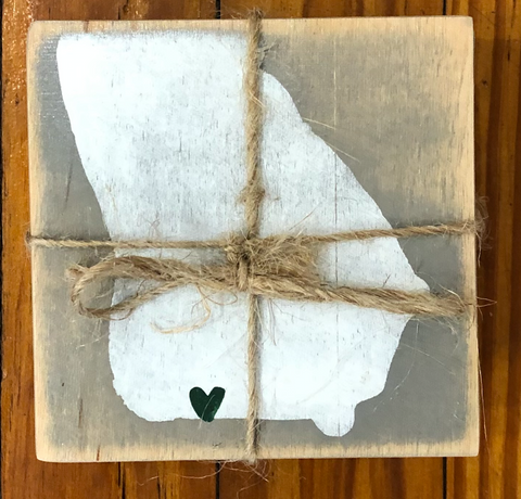 Pictured is a square coaster. On it is the silhouette of the state of Georgia over a grey background. At the bottom of the state is a green heart where Thomasville would be. The coaster has twine tied around it.