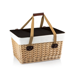 Pictured is the Canasta Grande Wicker Basket. It is rectangular in shape and made of a light wicker. The handles are long and tan fabric, attached to the base with black leather and black buttons. There is a leather wrap with elastic that can be used to hold the two handles together. The inside of the basket is lined with white fabric and that fabric folds over the edge of the basket. On top of the basket is a dark brown lid that doubles as a surface for food and drinks.