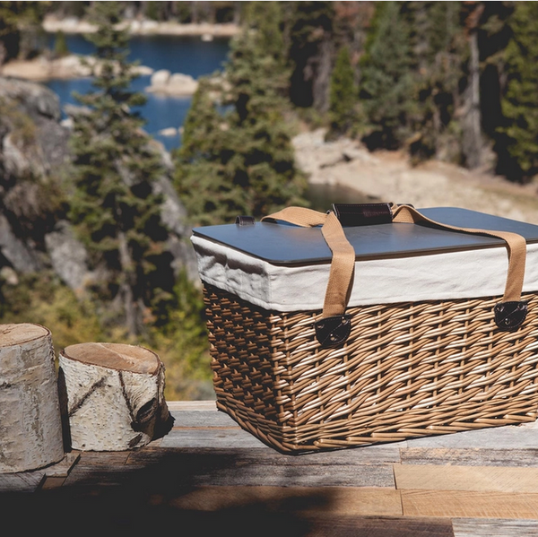 Pictured is a Canasta Grande Wicker Basket sitting on top of a table next to two cuttings from a Birch tree. In the background is a beautiful scene from a mountain river.