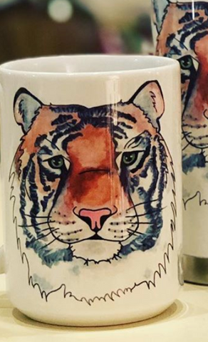 Pictured is a white coffee mug with a watercolor and pen & ink illustration of a tiger's face printed on it.