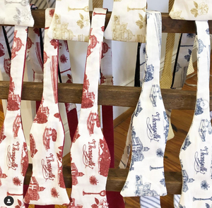 Pictured is a rack from which multiple bow ties hang from. The bow ties are all made of Toile of Thomasville fabric and are in a variet of colors.