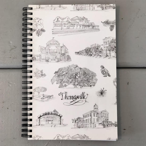 Pictured is a small spiral bound notebook with a black and white Toile of Thomasville cover.
